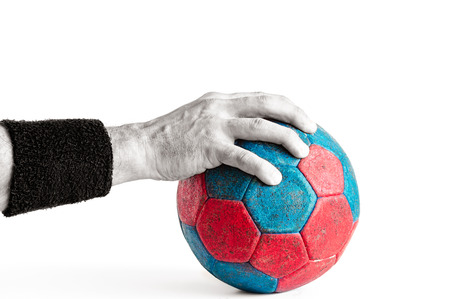 Mans hand on blue and red handball isolated on white, colored handball and black and white arm