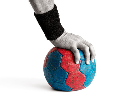 Mans hand pressing down on blue and red handball isolated on white, colored handball, desaturated hand