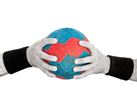 Man's hands on blue and red handball isolated on white, colored handball and desaturated hands Stock Photo