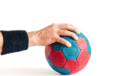 Mans hand on blue and red handball isolated on white Reklamní fotografie