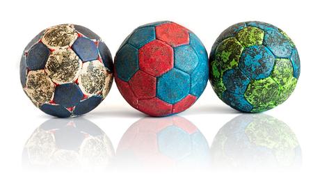 Rij van drie vuile handbalballen die op wit met bezinning worden geïsoleerd
