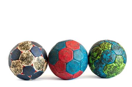 Fila de tres bolas sucias del balonmano aisladas en blanco, colorido, cubierto en resina del balonmano