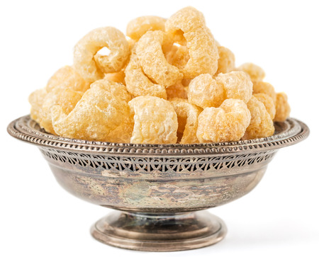 Antique metal bowl with crunchy pork cracklings isolated on white Reklamní fotografie - 95683631