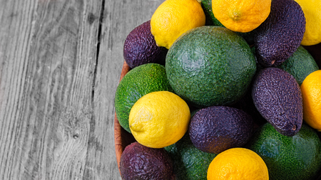 Top view of Hass avocados, Reed avocados and lemons in a fruit bowl on a gray wooden background