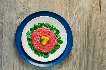 Top view of double plated beef steak tartare served with three raw quail egg yolks and surrounded by watercress leaves on a weathered gray wooden board Reklamní fotografie - 112473403