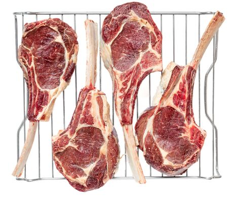 Top view of four frenched bone in veal tomahawk chops dry aging on a stainless steel rack.