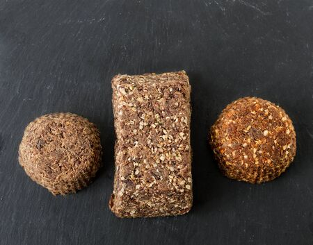 Top view of three bars of homemade beef meat and liver pemmican, plain with salt, with hemp seeds and hemp seeds and spices on a gray slate. Reklamní fotografie - 131576364