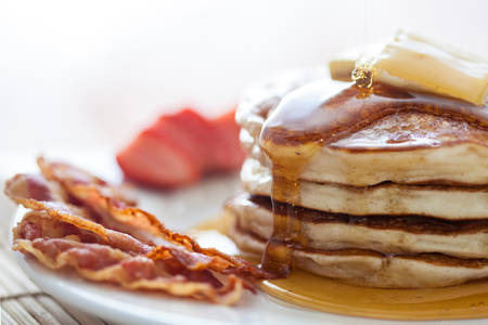 bacon: Pancakes with butter and honey served with bacon and strawberries