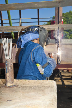 protective: Woman welding wearing protective clothes and equipment