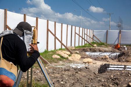 teodolito: Surveyor mirando a través del teodolito