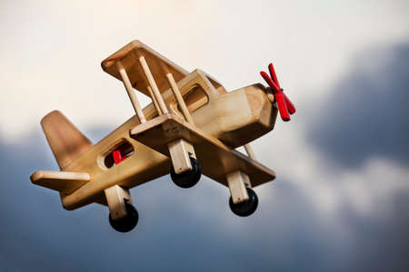 overcoming adversity: Wooden plane flying under the stormy sky - Going up