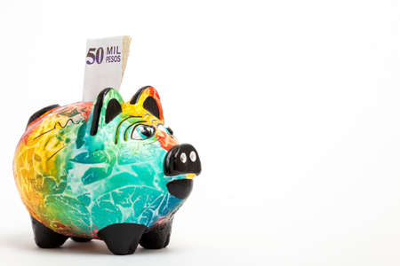 different goals: Saving colombian money in a Colorful piggy bank -  side view Stock Photo