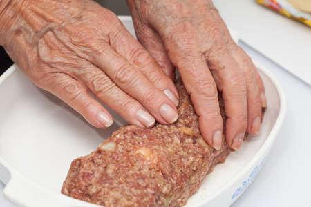 la conformación de un pastel de carne de huevo cruda y verduras rellenas Foto de archivo