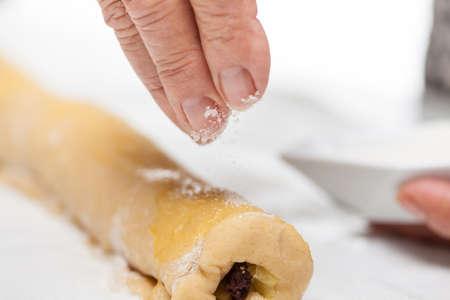 sprinkling: Sprinkling sugar over the rolled up strudel dough