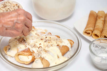 sprinkling: Sprinkling nuts over the crepes Stock Photo
