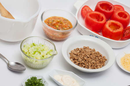 emptied: Stuffed tomatoes preparation : Cooked Ingredients to prepare stuffed tomatoes Stock Photo
