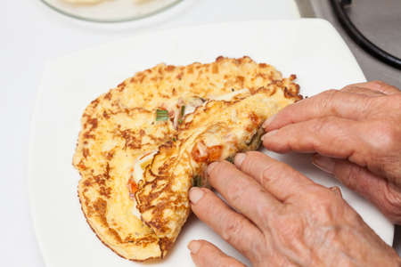 Omelet preparation : Rolling up the stuffed  omelet Banque d'images