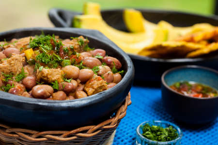 green bean: Beans with pork meat served with avocado and patacon on traditional black ceramic dishes