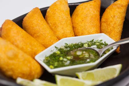 전형적인 콜롬비아 empanadas 매운 소스와 함께 전통적인 블랙 세라믹 접시에 재직했습니다.