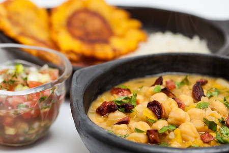 antioquia: Chickpeas with sausage served with patacon and rice Stock Photo