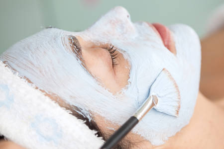 rejuvenate: Facial mask application on woman face using a brush