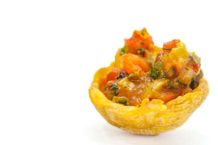creole: Plantain cup, made of crushed fried green plantains, filled with hogao on white background