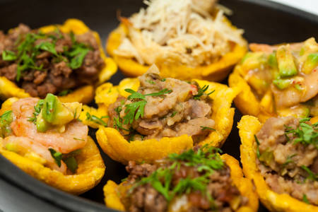 Plantain cups filled with different types of stuffing on black ceramic dish Stock Photo