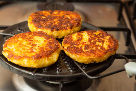 maize flour: Traditional Colombian Arepa de Choclo Preparation: Cornbreads being roasted on a round grill