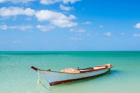 Canoe floating on calm water under beautiful blue sky Stock Photo