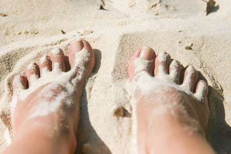 playa blanca: Close up of woman feet covered with white sand at the beach Stock Photo