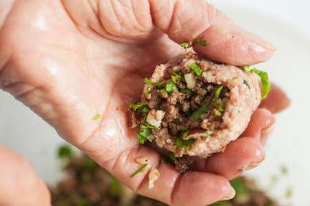 Step by step Levantine cuisine kibbeh preparation : Close up of a senior woman hands filling a kibbeh