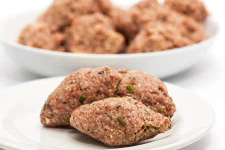 Step by step Levantine cuisine kibbeh preparation : Raw kibbeh balls on white dish Imagens