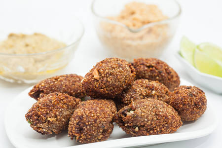Step by step Levantine cuisine kibbeh preparation : Ready fried kibbeh served with tahini and hummus Banco de Imagens