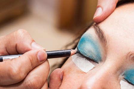 Make up artist using masking tape to create cat eyes