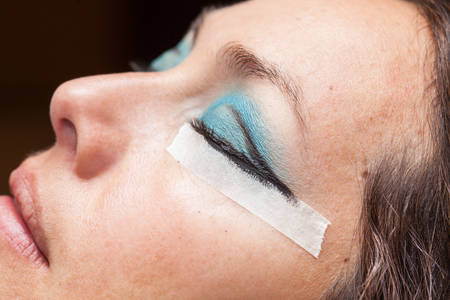 Close up of a woman while make up artist creates cat eyes