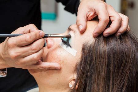 Make up artist creating cat eyes on a white woman
