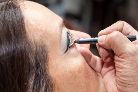 Makeup artist outlining white woman eyes Stock Photo