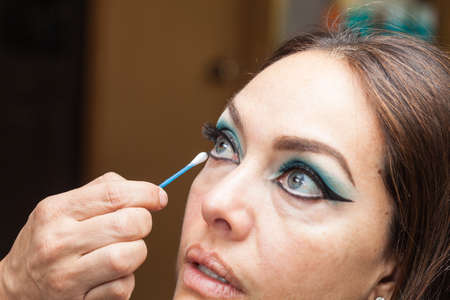 Makeup artist cleaning and giving the final touches to cat eyes makeup