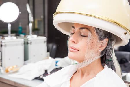 Woman under a professional hair steamer with a hair treatment