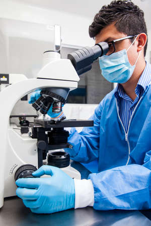 Young male scientist looking at slides under the microscope Stock Photo