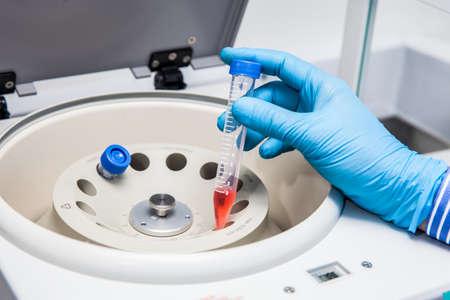 Scientist inserting a tube in a laboratory centrifuge