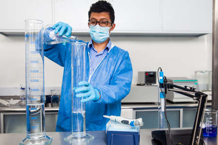 Young male scientist working at laboratory dressed in blue