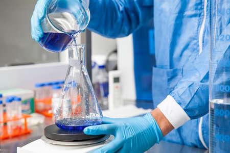 Jonge mannelijke wetenschapper die met een opruier werkt bij laboratorium gekleed in blauw Stockfoto