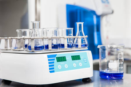 titration: Laboratory shaker loaded with erlenmeyers and beakers Stock Photo