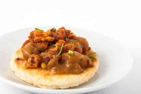 Traditional Colombian arepa topped with beans and pork rind Stock Photo