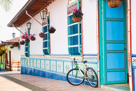 Bicycle next to a beautiful blue and white house at Guatape, Colombia