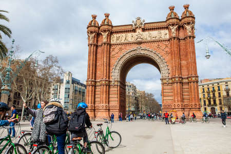 People on a bike tour at the Triumphal Arch in Barcelona Spain