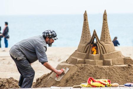 Sand sculptor working at La Barceloneta Beach in Barcelona Spain