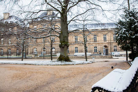 Bench covered with snow at the Luxembourg Palace garden in a freezing winter day day just before spring
