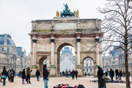 Street vendors at the Arch of Triumph and Louvre Museum in a freezing winter day just before spring Redakční
